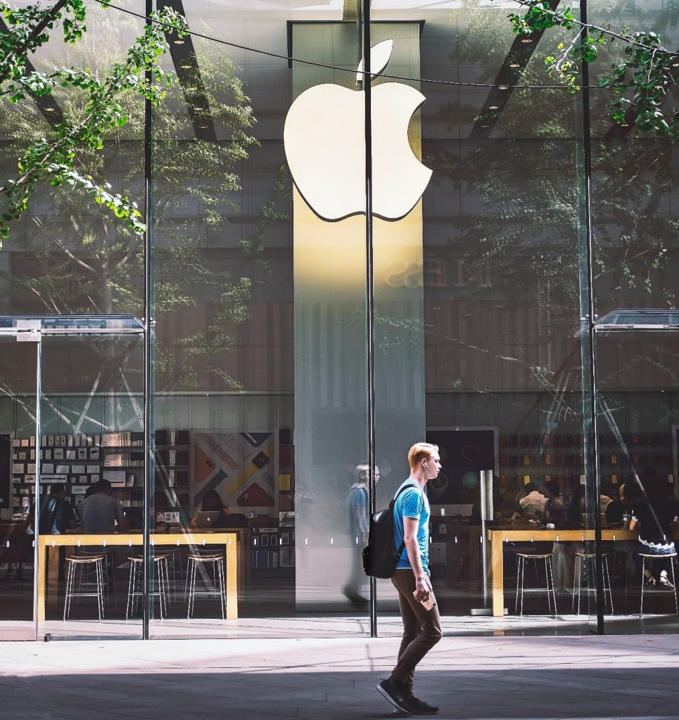 Man walking past an Apple store
